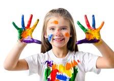 愉快的逗人喜爱的小女孩用五颜六色的被绘的手 免版税库存图片