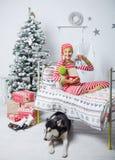 愉快的逗人喜爱的小孩男孩在家坐在装饰的新年室的镶边睡衣穿戴了 库存照片