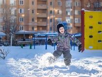 愉快的逗人喜爱的小孩男孩画象以五颜六色的温暖的冬天时尚穿衣 滑稽的孩子获得乐趣在森林或公园冷的da的 免版税库存照片