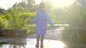 愉快的逗人喜爱的小男孩chid跑的使用获得跳跃通过水坑的乐趣在雨衣和胶靴 笑和 影视素材