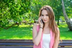 愉快的逗人喜爱的少妇微笑和谈话在电话在公园 图库摄影