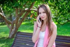 愉快的逗人喜爱的少妇微笑和谈话在电话在公园 库存图片