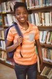 愉快的逗人喜爱的男孩画象在图书馆里 免版税库存图片