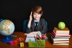 愉快的逗人喜爱的聪明的男孩坐在一块玻璃的一张书桌与举手 孩子准备回答与在backgro的一个黑板 免版税库存图片