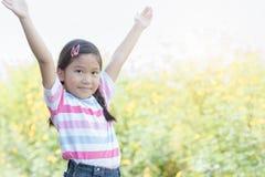 愉快的逗人喜爱的黄色花田的女孩微笑的妇女 库存照片