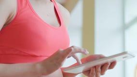 愉快的逗人喜爱的年轻女运动员开会和使用片剂在健身房 影视素材
