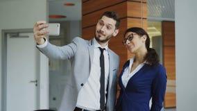 愉快的采取在smarphone照相机的商人和他的女性同事一selfie社会媒介的在现代办公室 股票视频