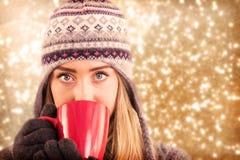 愉快的金发碧眼的女人的综合图象在冬天给拿着杯子穿衣 库存图片