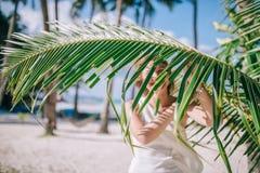 愉快的长的头发女孩画象有惊人的晒黑佩带的白色礼服的在好的绿色棕榈事假附近 免版税库存照片