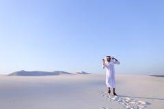 愉快的阿拉伯人在白色沙漠中部走并且享有生活o 库存图片