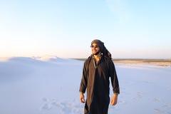愉快的阿拉伯人,步行通过沙漠,微笑并且享用锂 免版税图库摄影