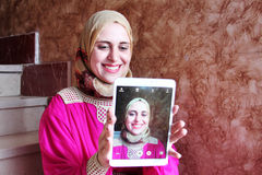 愉快的阿拉伯回教妇女佩带的hijab Selfie  免版税库存照片