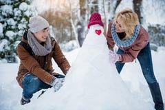 愉快的雕刻从雪的男人和妇女一个图 免版税图库摄影