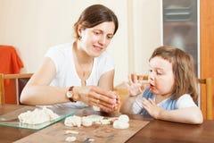 愉快的雕刻从黏土的母亲和婴孩在桌上 免版税库存图片