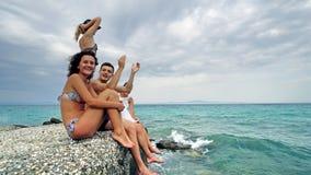 愉快的青少年坐有海滩的码头乐趣吹的亲吻和挥动手 免版税库存照片