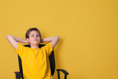 愉快的青少年的男孩画象向上看黄色的T恤杉的  库存照片