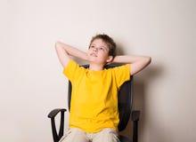 愉快的青少年的男孩画象黄色T恤杉的坐椅子 免版税图库摄影