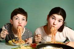 愉快的青少年的兄弟姐妹男孩和女孩吃意粉 免版税库存图片