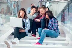 愉快的青少年的女孩和男孩台阶的学校或学院 免版税库存图片