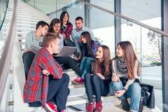 愉快的青少年的女孩和男孩台阶的学校或学院 免版税库存照片