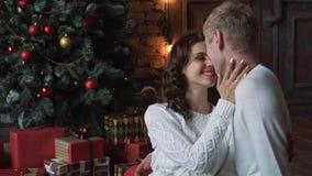 愉快的青年人由壁炉互相给礼物在圣诞树附近 股票录像