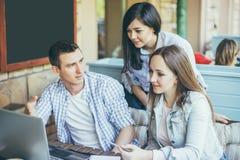 愉快的青年人画象在会议 一起研究一个创造性的项目的年轻设计师 免版税库存图片