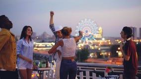 愉快的青年跳舞的慢动作在放松露天的党的举手和,当DJ混合音乐时 美丽的城市 影视素材