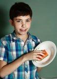 愉快的青春期前的男孩洗涤盘 免版税图库摄影
