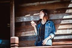 愉快的青年在智能手机的少年使用的和听的音乐 库存图片