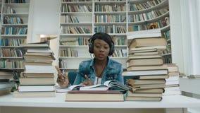 愉快的非洲在耳机的年轻女人听的音乐,当写演讲为大学时 影视素材