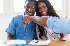 愉快的非裔美国人的夫妇得到新的家的钥匙 库存图片