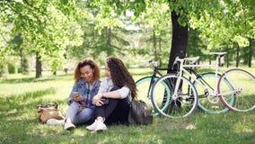 愉快的非裔美国人的妇女显示她的白种人朋友她的智能手机屏幕,女孩看它,谈话和 影视素材