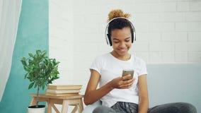 愉快的非裔美国人的妇女浏览有智能手机的互联网,并且笑的在家坐沙发,女孩听着 股票视频