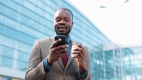 愉快的非裔美国人的成功的商人得到在智能手机的了不起的新闻 他在办公室中心附近站立 智能手机 股票录像
