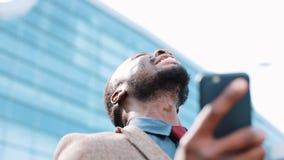 愉快的非裔美国人的成功的商人得到在智能手机的了不起的新闻 他在办公室中心附近站立 智能手机 影视素材