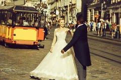 愉快的非裔美国人的新郎和逗人喜爱的新娘跳舞在街道上 免版税图库摄影