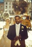 愉快的非裔美国人的走在街道上的新郎和逗人喜爱的新娘 图库摄影