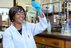 愉快的非洲女性研究员用玻璃设备 免版税库存图片