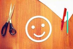 愉快的面带笑容由纸制成在书桌 免版税库存图片