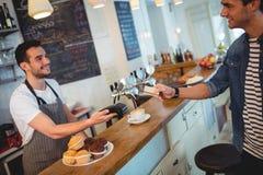 愉快的顾客和侍者在咖啡店 库存照片