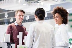 愉快的顾客谈话与两位有用的药剂师在一个当代药房 免版税库存照片