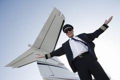 愉快的飞机上尉With Arms Out 免版税图库摄影