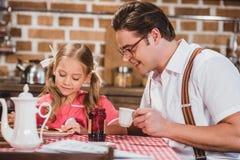 愉快的食用父亲和逗人喜爱的矮小的女儿早餐一起, 20世纪50年代 库存照片