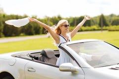 愉快的驾驶在敞蓬车汽车的男人和妇女 免版税图库摄影