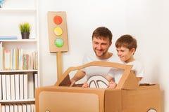 愉快的驾驶玩具纸板汽车的孩子和他的爸爸 免版税图库摄影