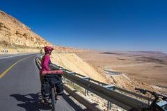 愉快的骑自行车的人在美丽的路放松在以色列沙漠 晴朗的热的天 免版税库存照片