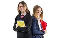 愉快的高中女朋友特写镜头画象 摆在照相机,在校服,有书和笔记本的,在白色背景 免版税库存照片