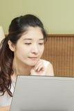愉快的年轻亚裔妇女与膝上型计算机一起使用在卧室 免版税库存照片