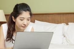 愉快的年轻亚裔妇女与膝上型计算机一起使用在卧室 免版税图库摄影