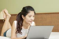 愉快的年轻亚裔妇女与膝上型计算机一起使用在卧室 库存照片